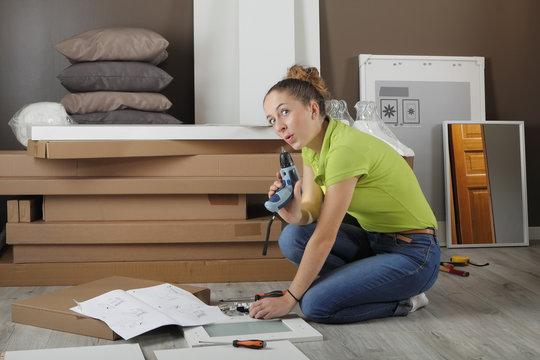 Jeune femme assemble meuble en kit