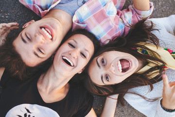 Closeup of three best friends lying down and laughing. Teenage people wearing casual clothes smiling. Top view