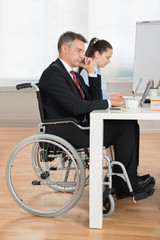 Disabled Businessman And Businesswoman In Conference Room