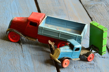 Set of vintage toys - trucks (lorries) toys on blue wooden background.
