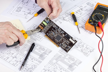 Electronics engineer using long nose plires to secure an interface plate to a computer card