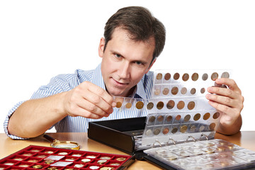 Man numismatist examines his collection of coin