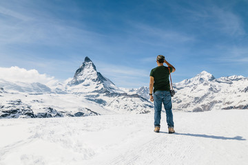 A man standing on the snow looking at the background of Matterho