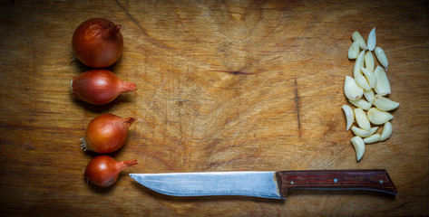 Onion, garlic and knife on a rustic wooden table.