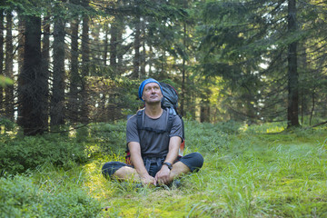 Hiker resting in a clearing in the pine forest, thinking about s
