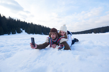 romantic couple have fun in fresh snow and taking selfie