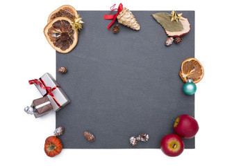 Plate of slate with different christmas decoration around it.