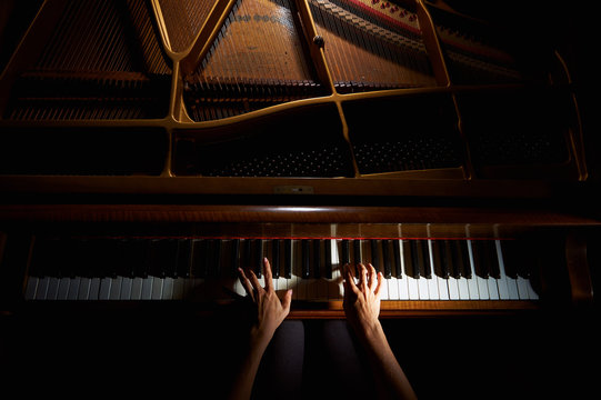 Woman's hands on the keyboard of the piano in night closeup