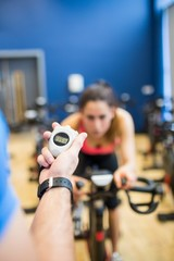 Trainer timing woman on exercise bike