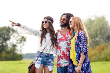 smiling young hippie friends on green field