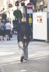 An elderly man is walking in the city. Some unidentified person are walking in the streets. Image has a vintage effect applied.