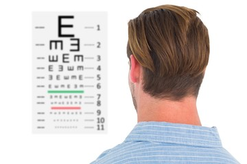 Composite image of focused man in suit on eye test letters