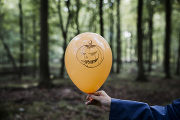 Hand holding a halloween balloon in the forest