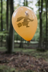 Orange halloween ballon with a witch illustration in the forest