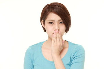 Japanese woman making the speak no evil gesture