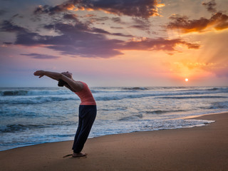 Young sporty fit woman doing yoga Surya Namaskar