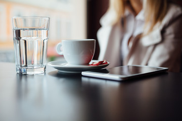 Woman in cafe with water, coffee and Tablet with copy space