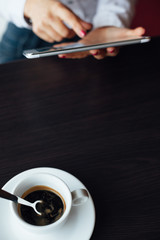Woman using tablet with cup of coffee on a table