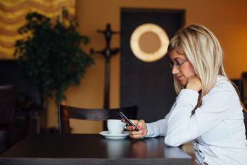 Side view of woman using new smart phone in a cafe