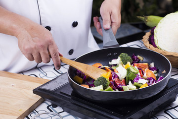 Chef cooking stir fried vegetable