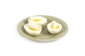 Boiled eggs with mayonnaise on a green plate isolated on white