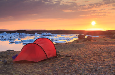 Fotomurales - Red tunnel tent during a beautiful sunrise at the Jokulsarlon lagoon on Iceland.