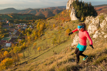 woman running on the trail above town with rocky terrain in the autumn