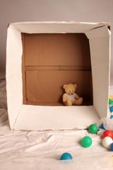 Teddybär sitzt in großer Kiste