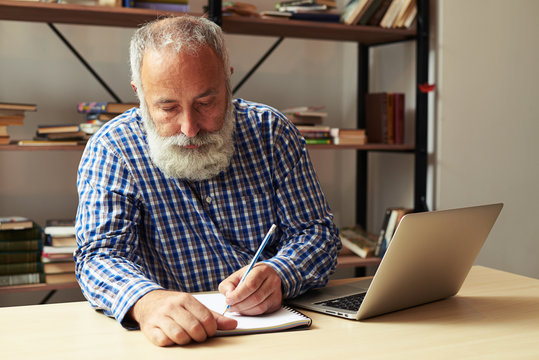 senior man writing in notepad at his working place