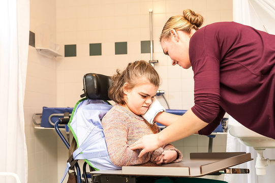 Disability/ A disabled child being cared for by a care assistant