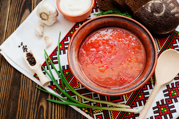 Ukrainian national cuisine , red borscht with sour cream , herbs , garlic and rye bread on a wooden background