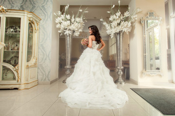 Bride in white wedding dress. Standing back to camera.
