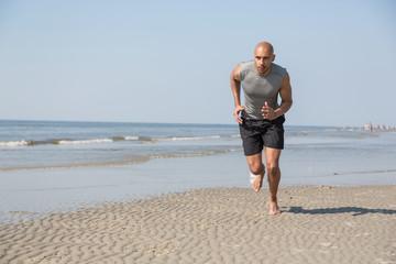 man running on a beach in summer sun