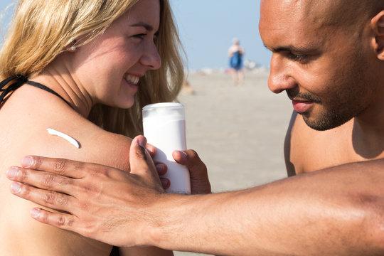 Man applying sunscreen to beautiful woman's shoulder