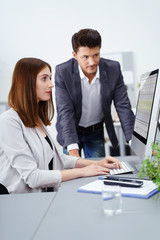 chef und mitarbeiterin schauen gemeinsam auf die zahlen am computer