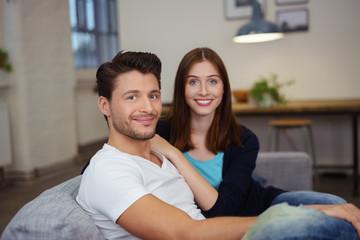 modernes paar sitzt entspannt lächelnd auf der couch