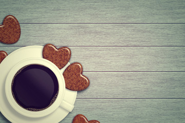 mug of coffee with heart cookies lying on wooden table