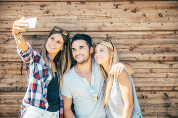 Funny selfie with friends. three cheerful young people making selfie and smiling while standing outdoors. wooden background