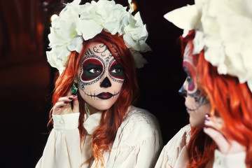 Young woman with Halloween sugar skull makeup looking on reflection in the mirror. Street portrait. Close up