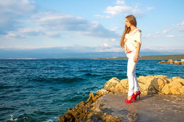 Beautiful young woman looking at the ocean.
