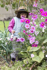 kid gardening concept - happy young child enjoying hiding in purple flowers with straw hat on in home vegetable garden in fall season, outdoors view