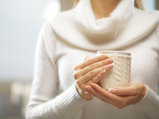 Woman hands with elegant french manicure nails design holding a cozy knitted mug. Winter and Christmas concept.