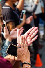 Frau in der Menschenmenge klatscht mit Smartphone in der Hand