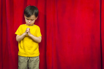 Mixed Race Boy Praying in Front of Red Curtain
