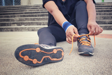 Woman hands tying shoelaces and listening to music with smart phone armband