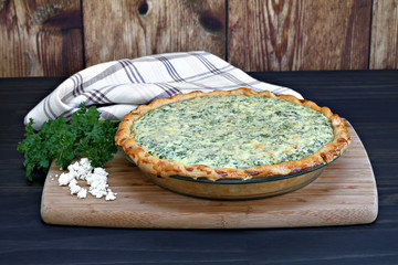 One whole spinach and feta cheese quiche on a cutting board.