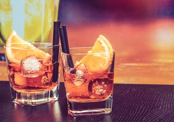 Fototapete - glasses of spritz aperitif aperol cocktail with orange slices and ice cubes on bar table, vintage atmosphere background