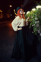Beautiful young woman wearing vintage clothes with Halloween sugar skull makeup. Full body night street portrait.