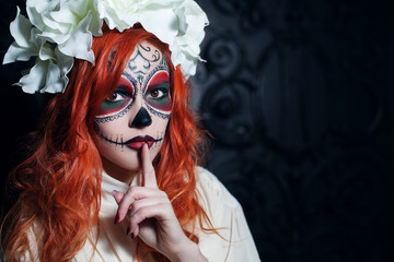 Beautiful young woman with halloween sugar skull makeup put forefinger to lips as sign of silence. Close up portrait. Dark  backgraund. Copy space, free text.