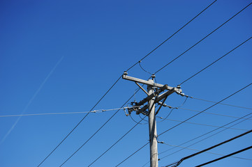 electricity pole against blue sky